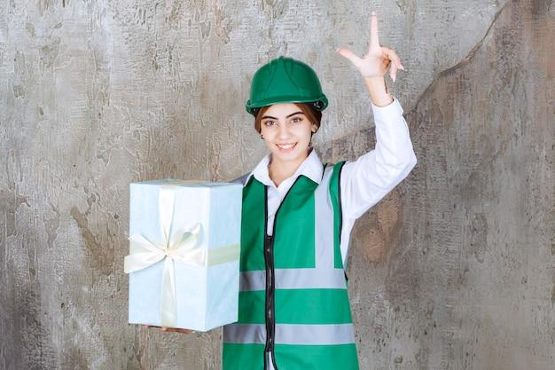 緑の制服と青いギフトボックスを保持し、良いアイデアを持っているヘルメットの女性エンジニア。