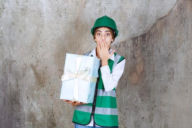 Женщина-инженер в зеленой форме и шлеме держит синюю подарочную коробку и выглядит смущенной и напуганной