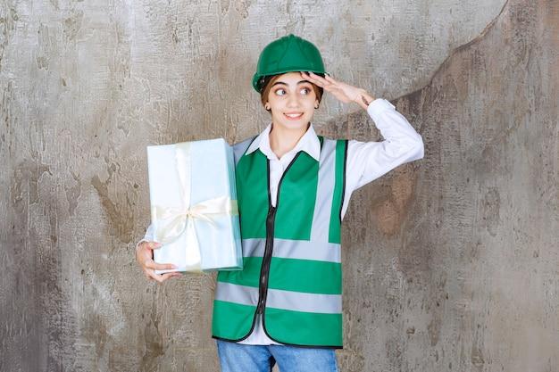 Женщина-инженер в зеленой форме и шлеме держит синюю подарочную коробку и замечает человека, который придет и получит ее.