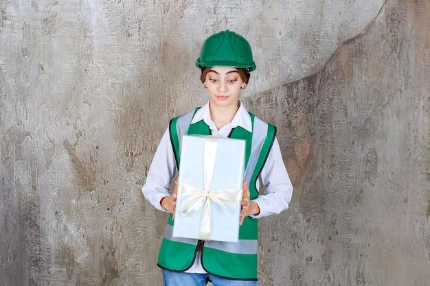 Женский инженер в зеленой форме и шлеме, держащем синюю подарочную коробку.