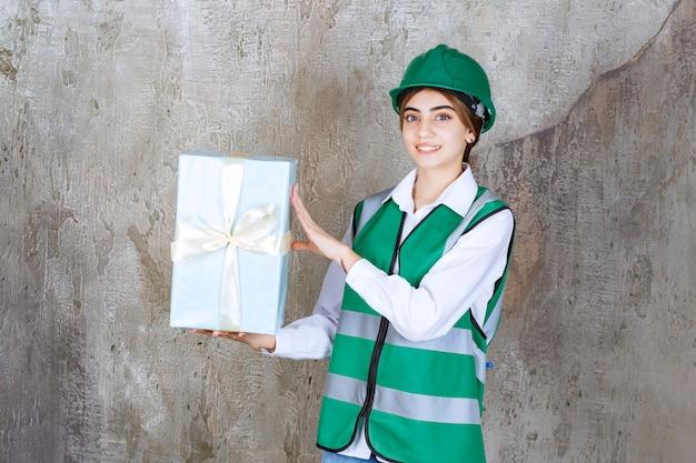 緑の制服と青いギフトボックスを保持しているヘルメットの女性エンジニア
