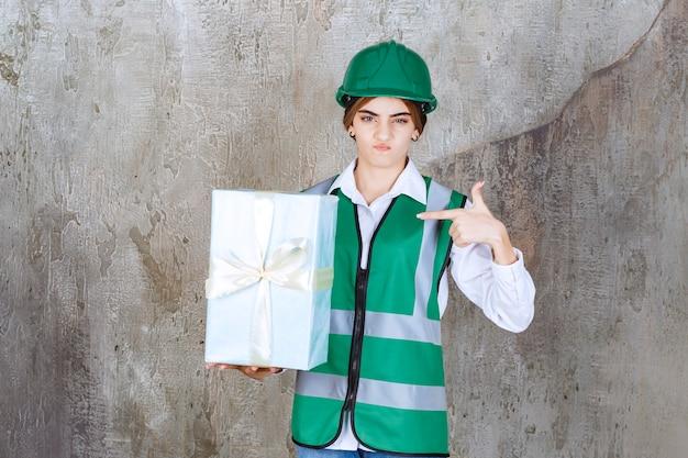 Женщина-инженер в зеленой форме и шлеме держит синюю подарочную коробку