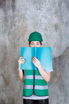 緑の制服と青いプロジェクトフォルダーを保持し、その後ろに顔を隠しているヘルメットの女性エンジニア。