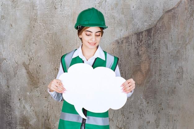 緑の制服と雲の形の情報ボードを保持しているヘルメットの女性エンジニア