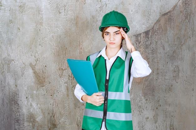 緑の制服と緑のプロジェクトフォルダーを保持し、疲れて眠そうに見えるヘルメットの女性エンジニア