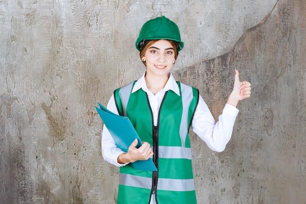 녹색 유니폼을 입은 여성 엔지니어와 녹색 프로젝트 폴더를 들고 긍정적인 손 기호를 보여주는 헬멧.
