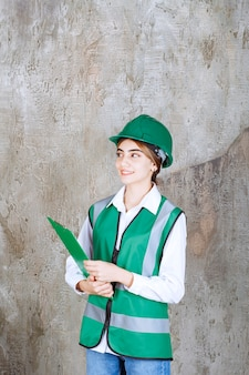 녹색 유니폼을 입은 여성 엔지니어와 녹색 프로젝트 폴더를 들고 있는 헬멧