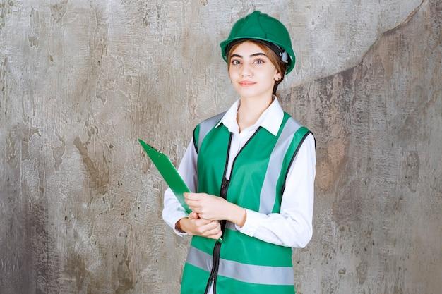 緑の制服と緑のプロジェクトフォルダーを保持しているヘルメットの女性エンジニア