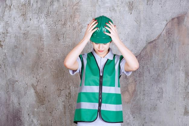 緑の制服とヘルメットの頭を保持し、おびえているように見える女性エンジニア