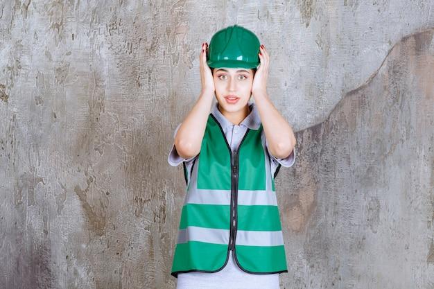 Женщина-инженер в зеленой форме и шлеме держит голову и выглядит напуганной.