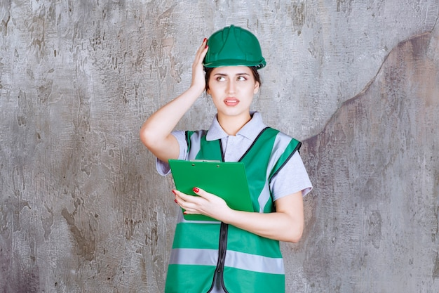 プロジェクトフォルダを保持し、おびえているように見える緑色の制服とヘルメットの女性エンジニア。