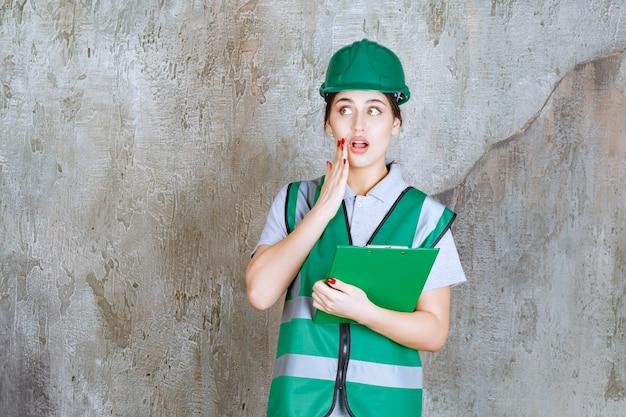 Женщина-инженер в зеленой форме и шлеме держит папку с проектом и выглядит напуганной.