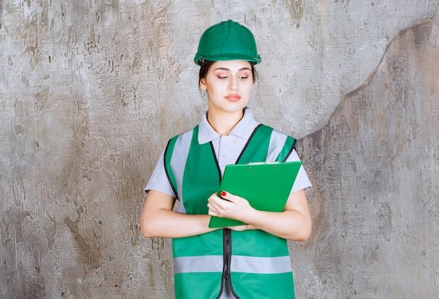 녹색 유니폼과 헬멧 프로젝트 폴더를 들고 여성 엔지니어.
