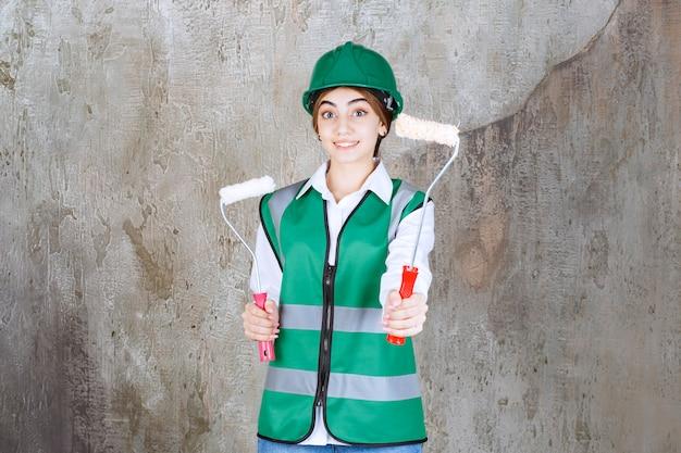 緑のユニフォームとヘルメットをかぶった女性エンジニアが、両手でペイントして同僚と共有するための2つのトリムローラーを持っています。