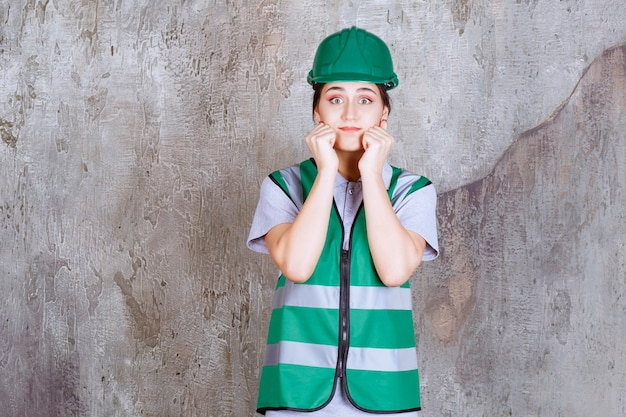 緑の制服とヘルメットの女性エンジニアは怖くて怖いように見えます。