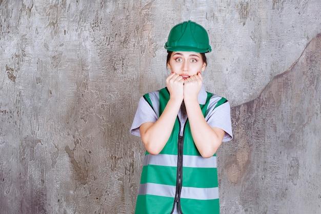 緑の制服とヘルメットの女性エンジニアは怖くて恐怖に見えます