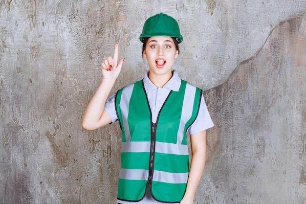 緑の制服と感情で上を指すヘルメットの女性エンジニア