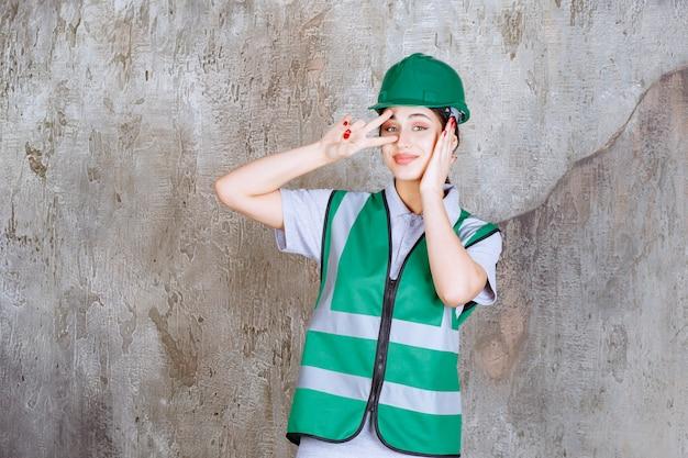 평화와 우정을 보내는 녹색 유니폼과 헬멧을 쓴 여성 엔지니어