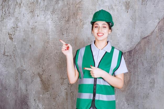 녹색 유니폼과 헬멧 왼쪽 감정을 보여주는 여성 엔지니어.