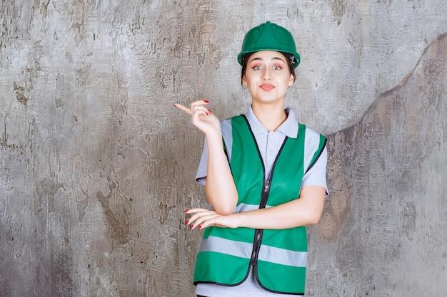 緑の制服とヘルメットの女性エンジニアが感情で左側を示しています