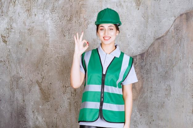 緑の制服とヘルメットの女性エンジニアは、肯定的な手のサインを示しています。
