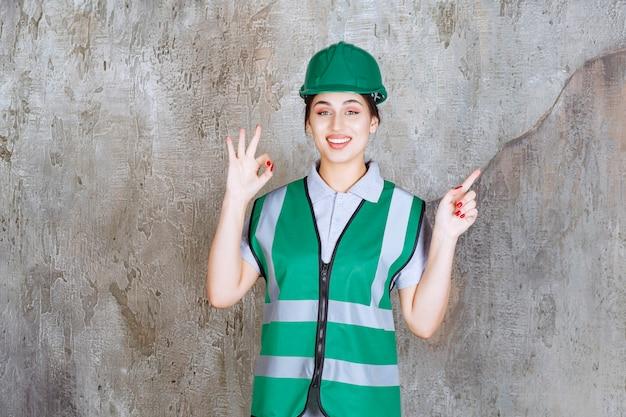 녹색 제복을 입은 여성 엔지니어와 긍정적인 손 기호를 보여주는 헬멧
