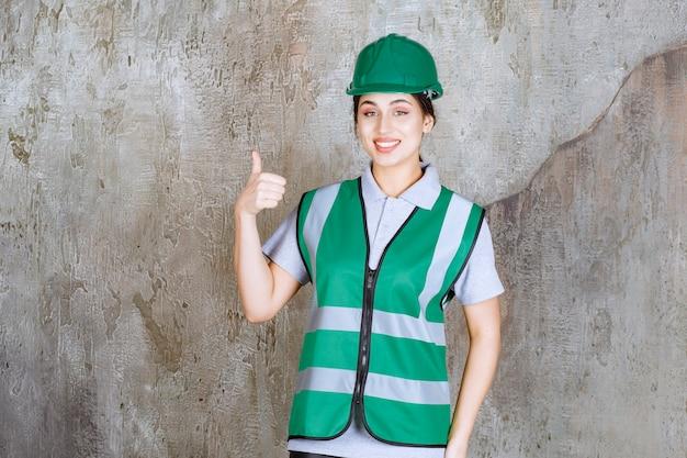 緑の制服とヘルメットの女性エンジニアは、肯定的な手のサインを示しています