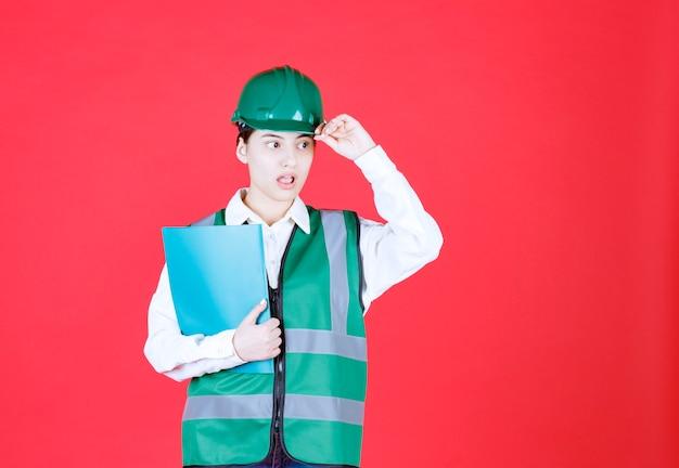 青いフォルダーを保持し、怖いと恐怖に見える緑の制服を着た女性エンジニア