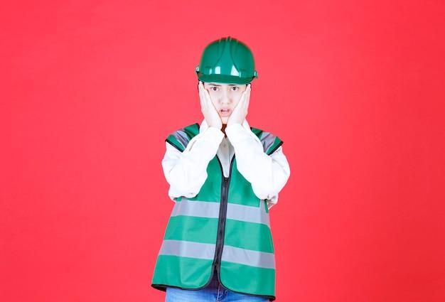 Женщина-инженер в зеленой форме выглядит усталой и разочарованной.