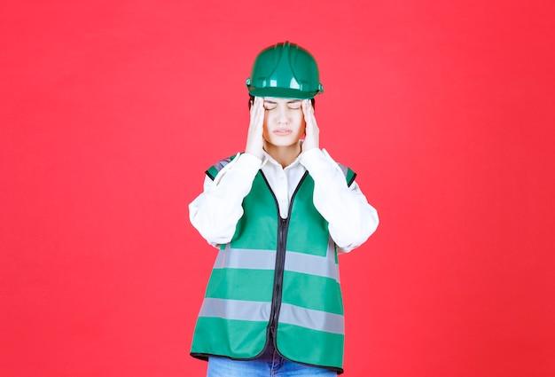 緑の制服を着た女性エンジニアは疲れてがっかりしているように見えます