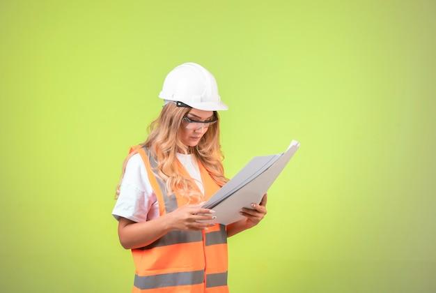 Женский инженер в шлеме и снаряжении, держа план проекта и проверяя его.