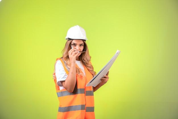 プロジェクト計画を保持し、眼鏡をかけているヘルメットとギアの女性エンジニア。