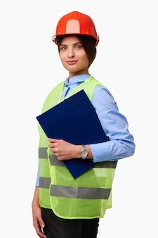 保護ヘルメットと白い孤立した背景の上の緑のベスト保持フォルダーの女性エンジニア