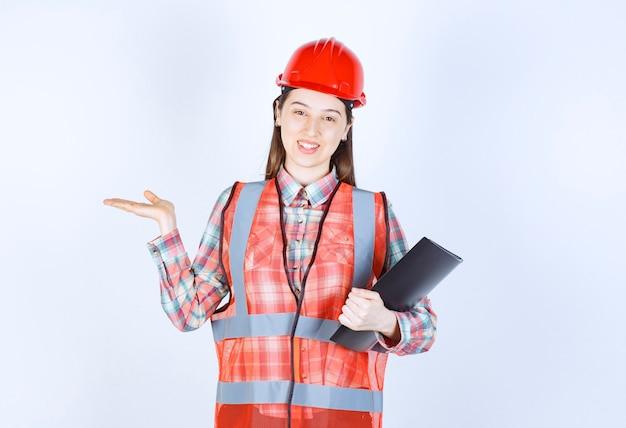 黒のプロジェクト計画を保持している赤いヘルメットの女性エンジニア。