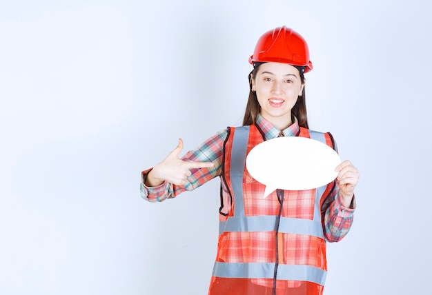 空白の情報ボードを保持している赤いヘルメットの女性エンジニア。