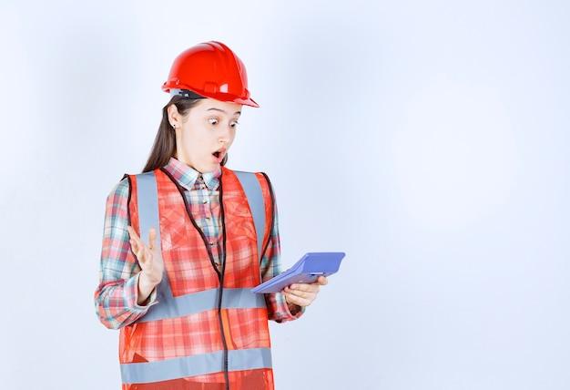 電卓に取り組んでいる赤いヘルメットの女性エンジニアは、混乱または興奮しているように見えます。