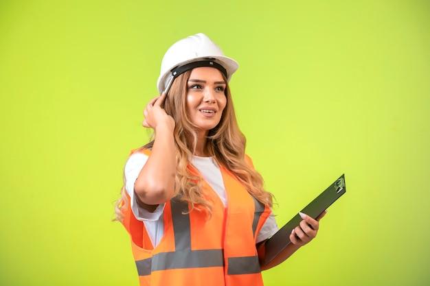 チェックリストを保持し、考えている白いヘルメットとギアの女性エンジニア。