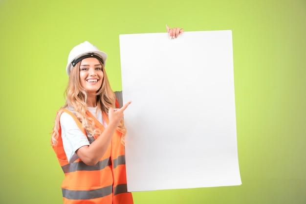 Женский инженер в белом шлеме и шестерне, представляя план строительства.
