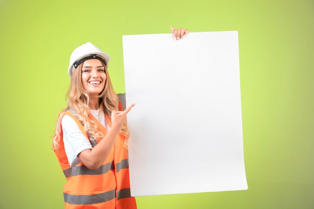 흰색 헬멧과 장비 건설 계획을 소개하는 여성 엔지니어