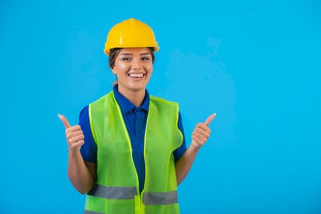 Женский инженер в желтом шлеме и шестерне делает большие пальцы руки вверх.