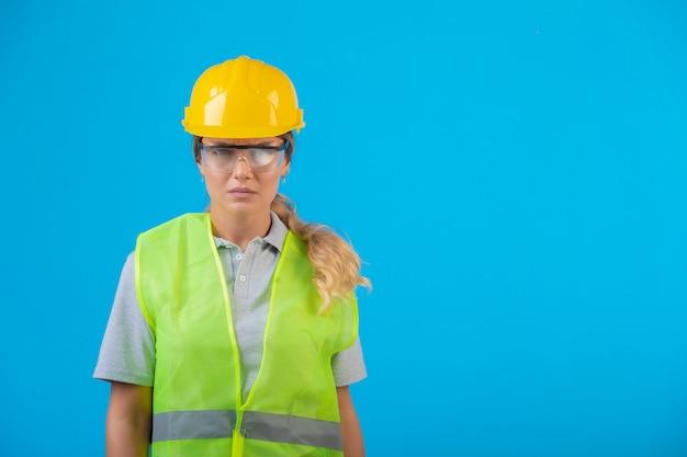 予防眼鏡をかけている黄色いヘルメットとギアの女性エンジニア。