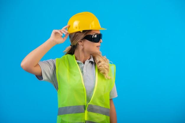 黄色いヘルメットとギアの女性エンジニアは、光線予防眼鏡をかけ、自信を持っています。