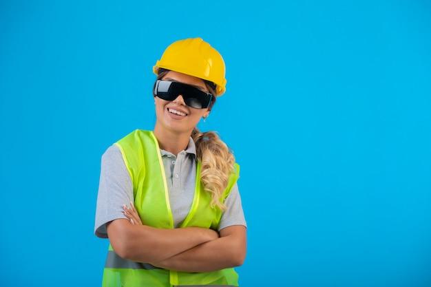 Инженер-женщина в желтом шлеме и снаряжении в лучевых профилактических очках, изображая из себя профессионала.