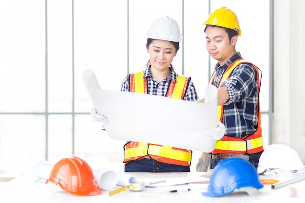 Female engineer look and discuss with male engineer about drawin