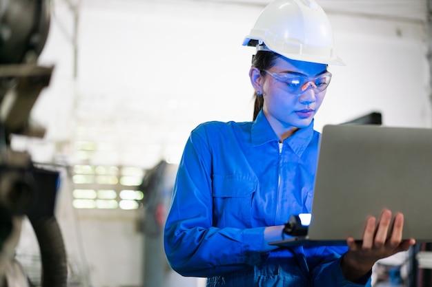 工場でのラップトップ コンピューター制御によるシステム溶接用のロボット アーム マシンをプログラミングする女性エンジニア