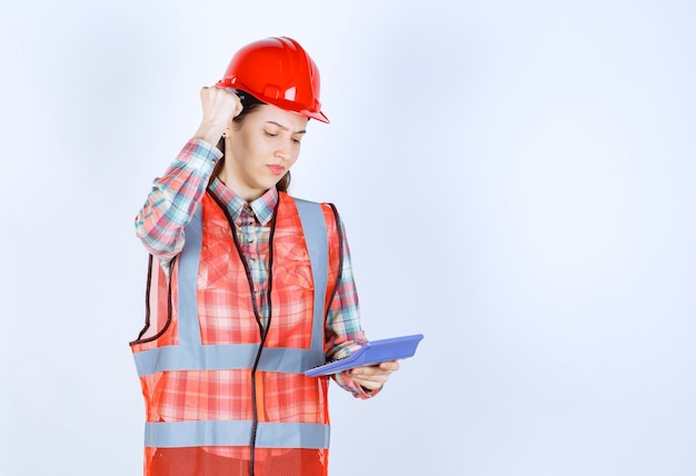 Female engineer in red helmet working on calculator and looks confused or thrilled.