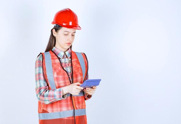 Female engineer in red helmet working on calculator.