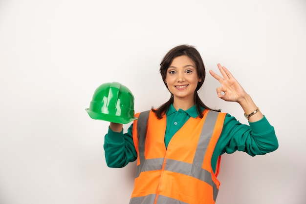 Female engineer showing ok gesture and holding a helmet on white background.