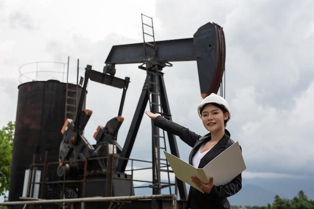 Женский инженер стоя около работающих масляных насосов с небом.