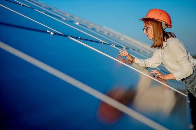 屋外のソーラーパネルの近くに立っている女性エンジニア